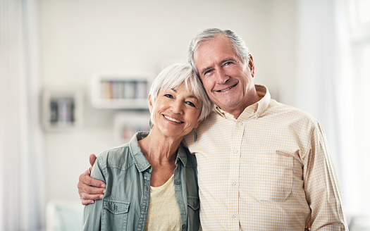 Elderly couple smiling with dentures at Optimum Oral Surgery Group.