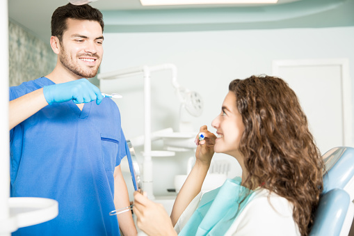 Dental hygienist showing patient proper oral hygiene techniques